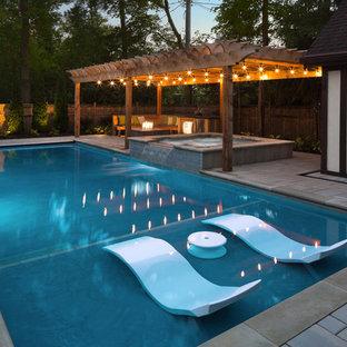 Foto de piscinas y jacuzzis clásicos, rectangulares, en patio trasero, con adoquines de hormigón