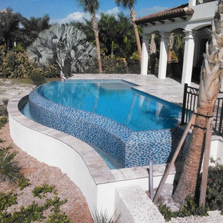 Hot tub - large contemporary backyard stone and custom-shaped aboveground hot tub idea in Miami