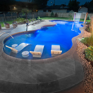 Pool house - large beach style side yard stamped concrete and custom-shaped natural pool house idea in Other