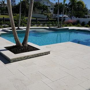 Ispirazione per una grande piscina naturale design personalizzata dietro casa con una dépendance a bordo piscina e pavimentazioni in pietra naturale