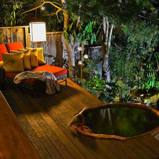 Ejemplo de piscinas y jacuzzis exóticos, pequeños, redondeados, en patio trasero, con entablado