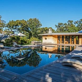 Esempio di una grande piscina monocorsia costiera rettangolare con una dépendance a bordo piscina e pedane