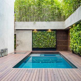 Immagine di una piscina design rettangolare in cortile con una vasca idromassaggio e pedane