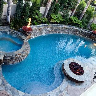 """Immagine di una piscina monocorsia tradizionale a """"C"""" dietro casa e di medie dimensioni con una vasca idromassaggio"""