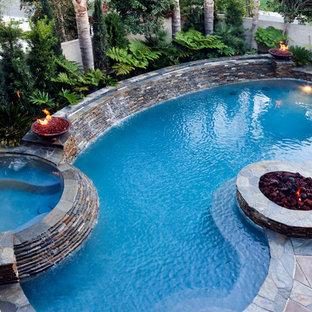 """Ispirazione per una piscina monocorsia chic a """"C"""" dietro casa e di medie dimensioni con una vasca idromassaggio e lastre di cemento"""