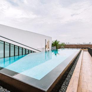 Diseño de piscina infinita, actual, rectangular, en azotea, con suelo de baldosas