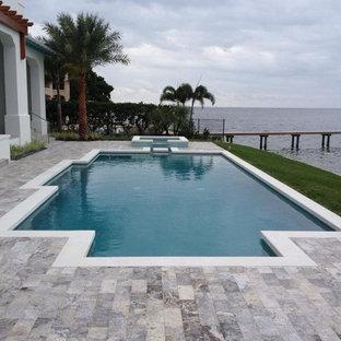 Imagen de piscina con fuente alargada, retro, de tamaño medio, a medida, en patio, con adoquines de piedra natural