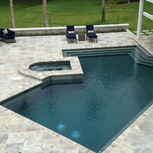 Foto de piscina alargada, exótica, grande, tipo riñón, en patio trasero, con adoquines de piedra natural