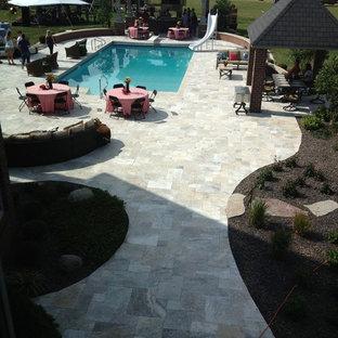 Modelo de piscina alargada, rústica, de tamaño medio, rectangular, en patio trasero, con adoquines de piedra natural