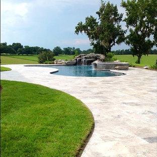 Diseño de piscina alargada, exótica, grande, tipo riñón, en patio trasero, con adoquines de piedra natural