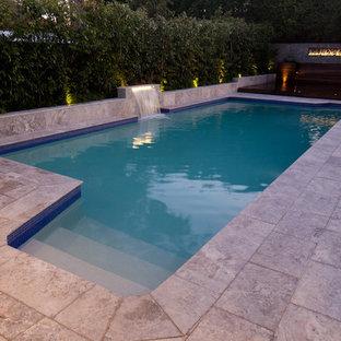 Ejemplo de piscina con fuente minimalista, de tamaño medio, rectangular, en patio trasero, con adoquines de piedra natural