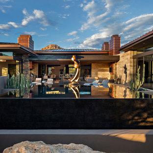 Foto på en stor funkis infinitypool på baksidan av huset, med spabad och kakelplattor