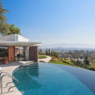 Ejemplo de piscina infinita, vintage, redondeada, con losas de hormigón