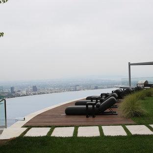 Esempio di una piscina a sfioro infinito contemporanea personalizzata dietro casa con pedane