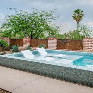 Modelo de piscina de estilo americano, pequeña, rectangular, en patio trasero, con losas de hormigón
