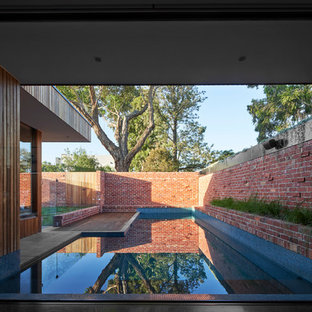 Inspiration for a contemporary custom-shaped pool in Melbourne with brick pavers.