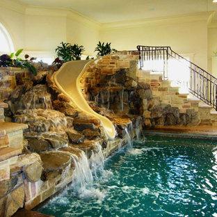 Idee per una piscina coperta american style rettangolare con pavimentazioni in pietra naturale e un acquascivolo