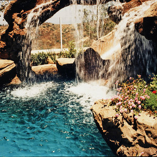 World-inspired back custom shaped swimming pool in Orange County with a water slide and stamped concrete.