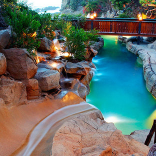 Huge island style backyard stamped concrete and custom-shaped water slide photo in Orange County