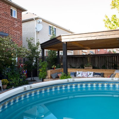Example of a mid-sized arts and crafts backyard round and concrete paver aboveground pool fountain design in Toronto
