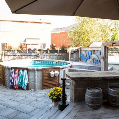 Inspiration for a mid-sized craftsman backyard pool fountain remodel in Toronto with decking