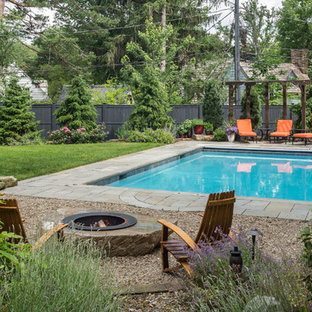 Design ideas for a mid-sized traditional backyard rectangular lap pool in Cleveland with a water feature and natural stone pavers.