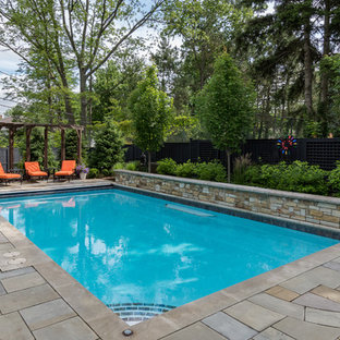 Photo of a mid-sized traditional backyard rectangular lap pool in Cleveland with a water feature and natural stone pavers.