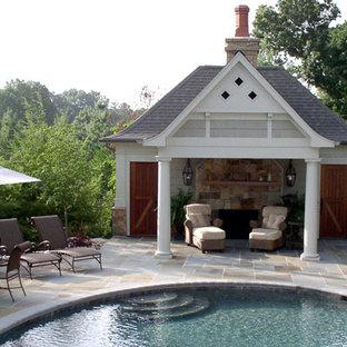 Modelo de piscina natural, de estilo americano, de tamaño medio, redondeada, en patio trasero, con adoquines de piedra natural