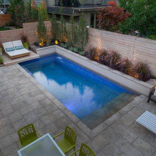 Diseño de piscina con fuente clásica, pequeña, rectangular, en patio trasero, con adoquines de piedra natural