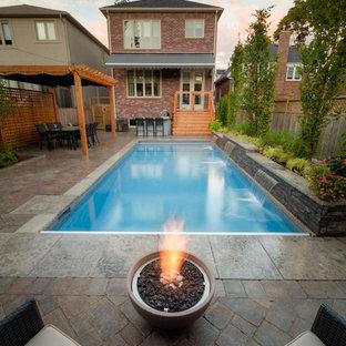 Imagen de piscina con fuente tradicional, de tamaño medio, rectangular, en patio trasero, con adoquines de piedra natural
