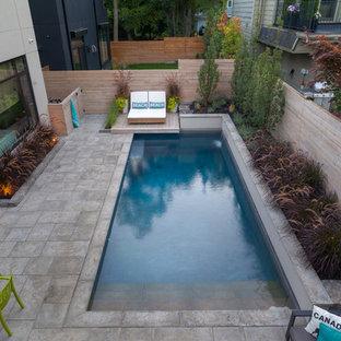 Ejemplo de piscina con fuente clásica, pequeña, rectangular, en patio trasero, con adoquines de piedra natural