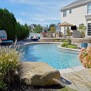 Modelo de piscina con fuente romántica, a medida, en patio trasero, con adoquines de hormigón