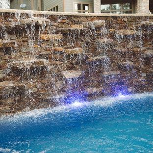 Réalisation d'une grand piscine arrière craftsman sur mesure avec un point d'eau et des pavés en pierre naturelle.