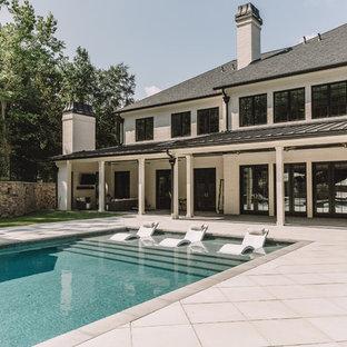 Diseño de piscina alargada, tradicional renovada, rectangular, en patio trasero, con adoquines de hormigón