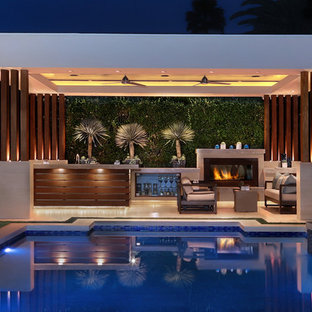 Example of a large trendy backyard stone and rectangular hot tub design in Orange County