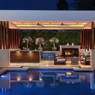 Cette image montre une grande piscine arrière design rectangle avec des pavés en pierre naturelle et un bain bouillonnant.