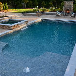 Imagen de piscinas y jacuzzis alargados, de estilo americano, grandes, rectangulares, en patio trasero, con adoquines de hormigón