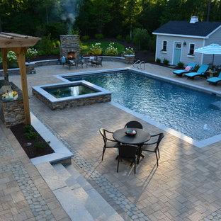 Foto de piscinas y jacuzzis alargados, clásicos, grandes, rectangulares, en patio trasero, con adoquines de hormigón