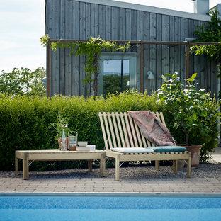Ejemplo de piscina elevada, escandinava, de tamaño medio, rectangular, con adoquines de ladrillo