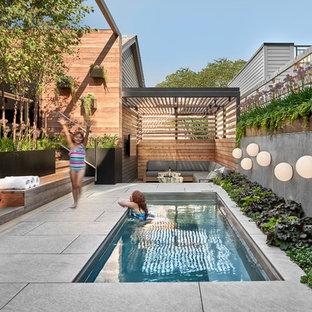 Diseño de piscina contemporánea, en patio trasero, con suelo de baldosas