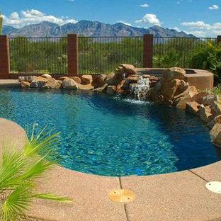 Ejemplo de piscinas y jacuzzis naturales, de estilo americano, de tamaño medio, a medida, en patio trasero, con adoquines de hormigón