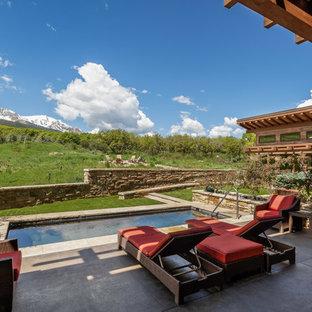 Diseño de piscina alargada, rústica, rectangular, en patio trasero, con losas de hormigón