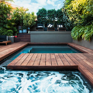 This is an example of a tropical backyard custom-shaped lap pool in Perth with a hot tub and decking.
