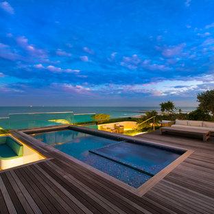 Cette image montre une grand piscine minimaliste rectangle avec un bain bouillonnant.