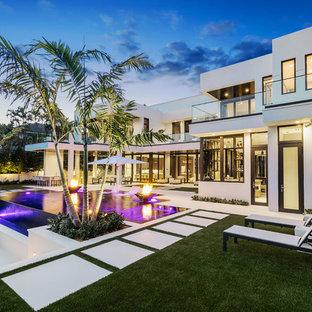 Modelo de piscinas y jacuzzis infinitos, modernos, grandes, rectangulares, en patio trasero, con suelo de baldosas