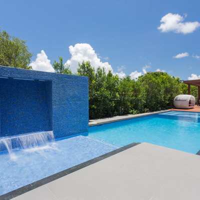 Inspiration for a mid-sized contemporary backyard stamped concrete and rectangular lap pool fountain remodel in Miami