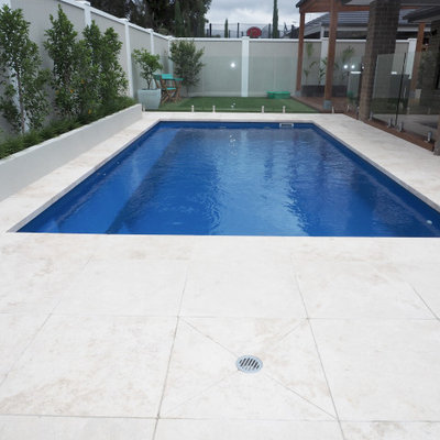 Pool landscaping - mid-sized modern backyard stone and rectangular natural pool landscaping idea in Melbourne