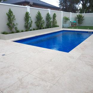 Imagen de piscina natural, minimalista, de tamaño medio, rectangular, en patio trasero, con adoquines de piedra natural