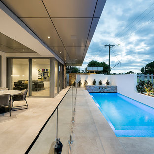 Design ideas for a large contemporary backyard rectangular lap pool in Perth with a water feature.