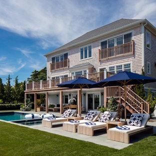 Ejemplo de piscinas y jacuzzis costeros, grandes, rectangulares, en patio trasero, con losas de hormigón